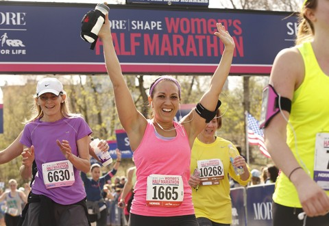 Runner celebrates crossing the finish line at the 2015 MORE/SHAPE Women's Half-Marathon