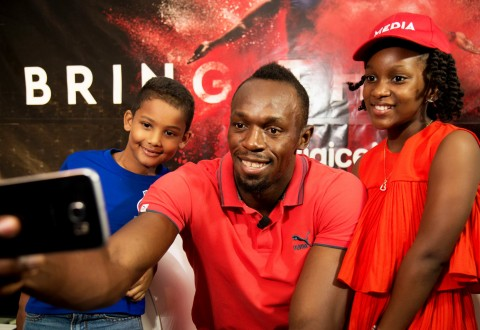"Seven year-old Ajani Brown from Jamaica scores a selfie with Usain Bolt and kiddie moderator for the Digicel ""Bring the Beat""; press conference, nine year-old Naleighna-Kae McLean. (PRNewsFoto/Digicel Group)"