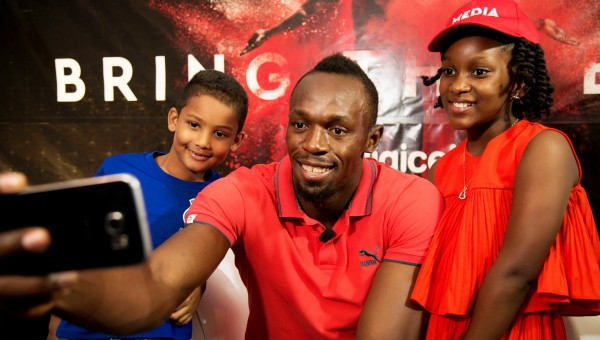 """Seven year-old Ajani Brown from Jamaica scores a selfie with Usain Bolt and kiddie moderator for the Digicel """"Bring the Beat""""; press conference, nine year-old Naleighna-Kae McLean. (PRNewsFoto/Digicel Group)"""