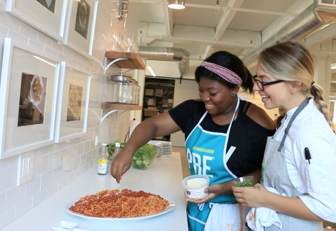 Sarah Russo, Culinary Manager of Chicago-based food startup PRE(r) Brands, guides a Common Threads student through a cooking lesson at PRE's kitchen in Chicago's River North neighborhood.